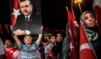 TOPSHOT - A man holds up a photo of Turkey's President Recep Tayyip Erdogan during a Pro-Erdogan rally in Taksim square in Istanbul on July 22, 2016, following the failed military coup attempt of July 15.  Turkey detained 283 members of the presidential guard of Recep Tayyip Erdogan after last week's attempted coup, a government official said July 22. The guard are members of the special forces regiment stationed at the presidential palace in Ankara. There are at least 2,500 members, according to local media.  / AFP / OZAN KOSE        (Photo credit should read OZAN KOSE/AFP/Getty Images)