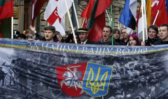 "Right wing protesters march organized by nationalist parties during a celebration of Lithuania's independence in Vilnius, Lithuania, Wednesday, March 11, 2015. Lithuania celebrated the 25th anniversary of its declaration of independence from the Soviet Union on Wednesday, recalling the seminal events that set the Baltic nation on a path to freedom and helped lead to the collapse of the U.S.S.R. The poster reads: ""For Our and Your Freedom"". (AP Photo/Mindaugas Kulbis)"
