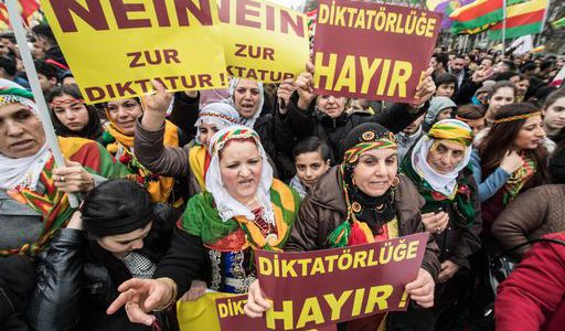 "Kurdish protesters demonstrate on their way to the Kurdish spring festival Newroz with posters reading  ""No to dictatorship""  in the city center of Frankfurt am Main, western Germany, on March 18, 2017. / AFP PHOTO / dpa / Boris Roessler / Germany OUT"