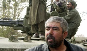 FILE - Afghan Gen. Rashid Dostum glances at reporters upon his arrival at a fortress prison near Mazar-e-Sharif, northern Afghanistan, Wednesday, Nov. 28, 2001. Dostum, a powerful anti-Taliban leader, spoke out on Thursday Dec.6, 2001,  against the landmark power-sharing agreement reached in Germany this week, saying he would boycott the new Afghan government.   Mullah Mohammed Omar, the Taliban leader,  agreed Thursday Dec. 6 2001 to hand control of the militia's last bastion Kandahar to an oppositioncommander, Mullah Naqib Ullah,  The Afghan Islamic Press reported.  (AP Photo/Darko Bandic)