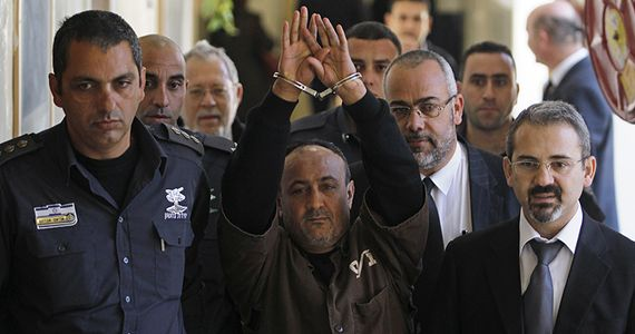 An Israeli prison guard escorts jailed Fatah leader Marwan Barghouti (C) to a deliberation at Jerusalem Magistrate's court January 25, 2012. Convicted of murder for his role in attacks on Israelis, Barghouti was jailed for life by Israel in 2004.  REUTERS/Baz Ratner (JERUSALEM - Tags: POLITICS CRIME LAW) - RTR2WTIC