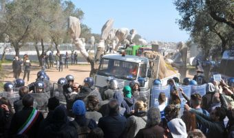 Un momento del trasporto degli ulivi espiantati durante la protesta degli attivisti davanti al cantiere della Tap a Melendugno, nel Leccese, contro il progetto di approdo del gasdotto dell'Adriatico, con agenti di polizia in assetto antisommossa che fronteggiano i manifestanti, 29 marzo 2017. ANSA/ CLAUDIO LONGO